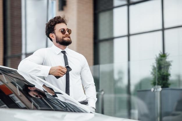 Knappe, glimlachende, gelukkige, bebaarde zakenman gebruikt zijn mobiele telefoon en staat buiten op straat in de buurt van zijn auto