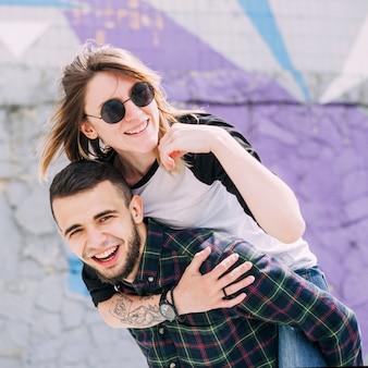 Knappe glimlachende jonge mens die haar piggy rit op zijn rug neemt