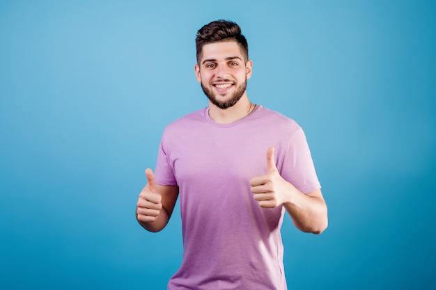 Knappe glimlachende kerel die duimen tonen die omhoog op blauw worden geïsoleerd
