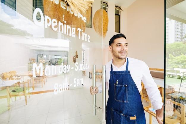 Knappe glimlachende kleine ondernemer cafédeur openen en klanten verwelkomen