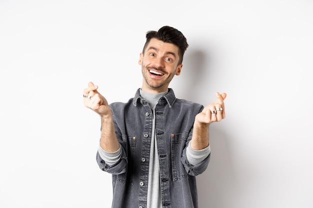 Knappe glimlachende man die handharten toont en met liefde naar de camera kijkt, staande op een witte achtergrond