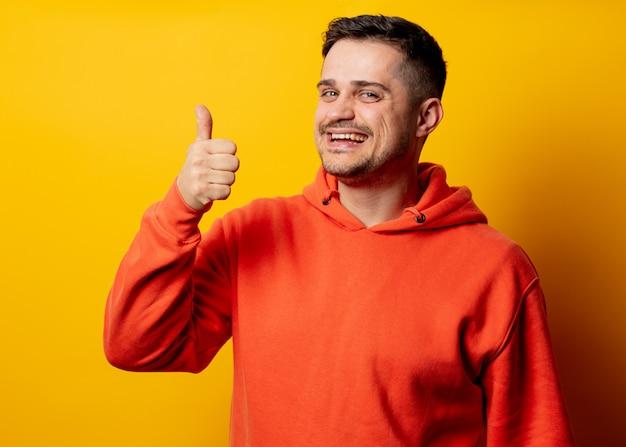 Knappe glimlachende man in hoodie op gele muur