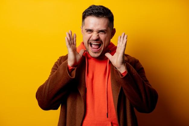 Knappe glimlachende man in jas op gele muur