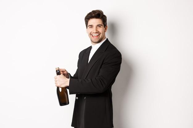 Knappe glimlachende man in trendy pak opent een fles champagne, viert vakantie, staande op een witte achtergrond