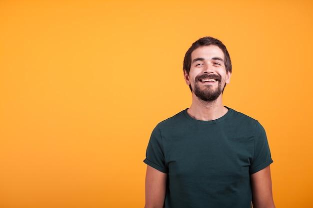 Knappe glimlachende man met armen op zijn rug op oranje achtergrond in studio. portret van een vrolijke, modieuze man die naar de camera kijkt
