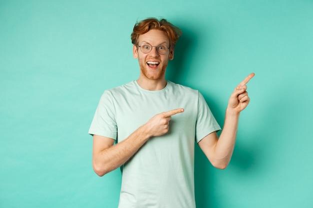Knappe glimlachende man met rood haar en baard, geamuseerd kijkend en wijzend naar de rechterbovenhoek, met promo-aanbieding, staande over mint achtergrond