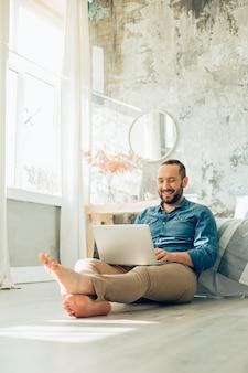 Knappe glimlachende man op blote voeten met laptop op de vloer die thuis online werkt