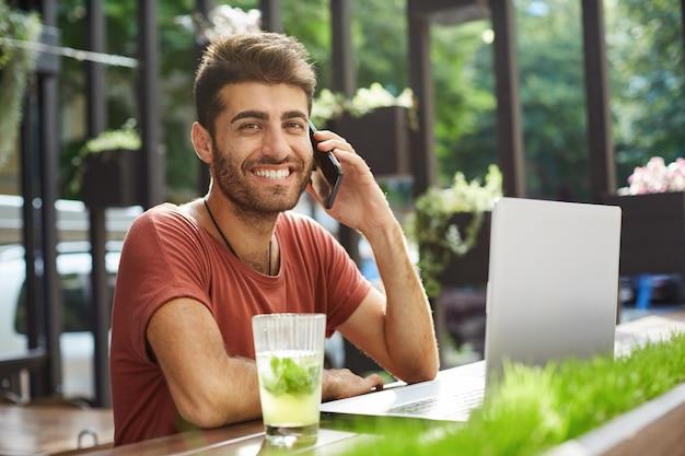 Knappe glimlachende man praten op de mobiele telefoon, de verkoper bellen die hij online vond tijdens het gebruik van laptop, winkelen, appartement op internet zoeken
