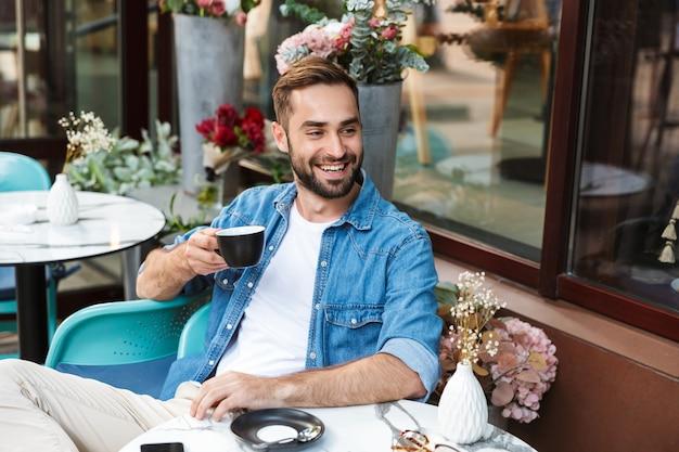 Knappe glimlachende man zit aan de cafétafel buiten en drinkt koffie