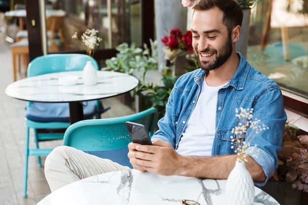 Knappe glimlachende man zit aan de cafétafel buiten, met behulp van mobiele telefoon