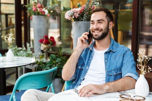 Knappe glimlachende man zit aan de cafétafel buiten, pratend op mobiele telefoon