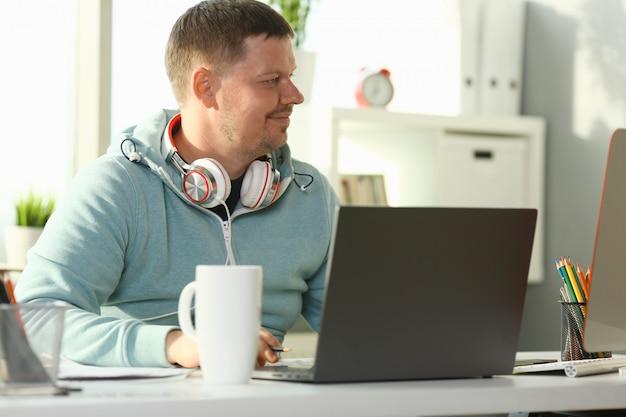 Knappe glimlachende mannelijke student die online gebruikt