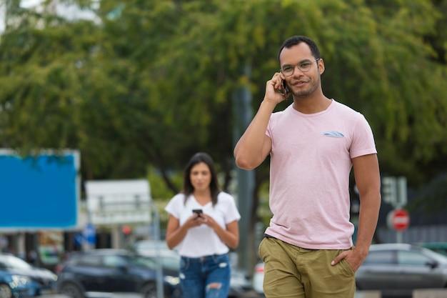 Knappe glimlachende mens die op telefoon spreekt terwijl het lopen op straat
