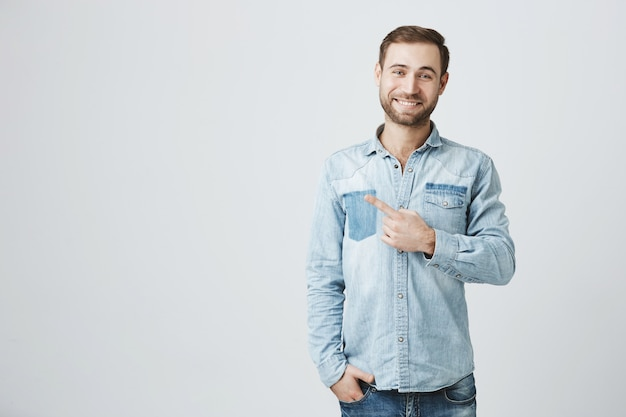 Knappe glimlachende mens die promo aantoont, die links richt