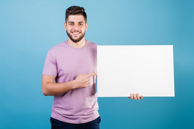 Knappe glimlachende mens die vinger op wit exemplaar ruimtedocument richten dat op blauw wordt geïsoleerd