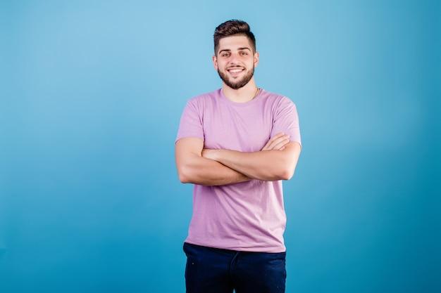 Knappe glimlachende mens met handen die op borst worden gekruist die op blauw wordt geïsoleerd