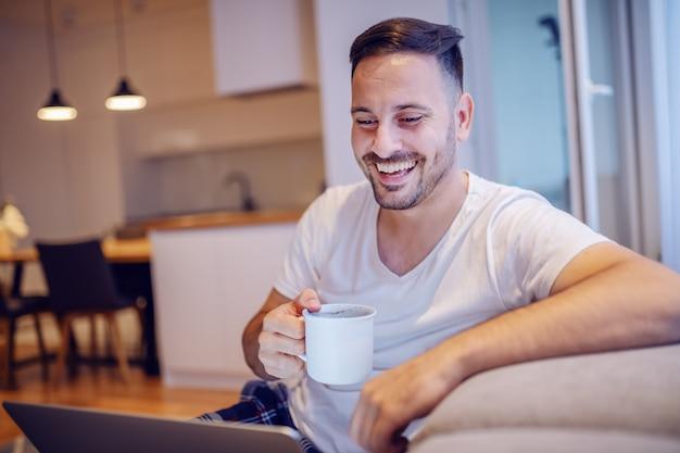 Knappe glimlachende ongeschoren kaukasische mens die in pyjama's in woonkamer met laptop in overlapping zitten en zijn verse ochtendkoffie drinken.