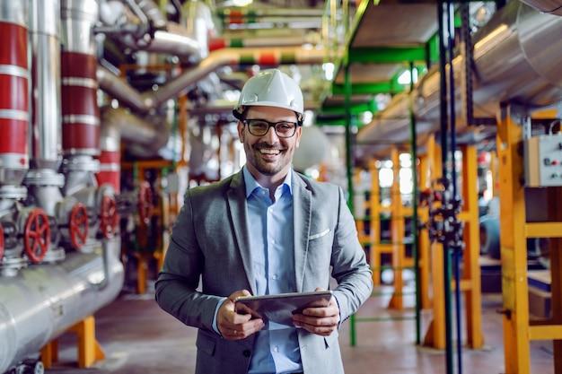 Knappe glimlachende supervisor in grijs kostuum en met witte helm op hoofdholdingstablet. elektriciteitscentrale interieur.