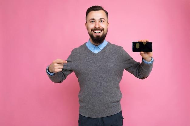 Knappe glimlachende volwassen mannelijke persoon knap gekleed in een casual outfit staand