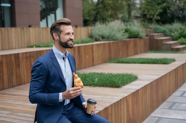 Knappe glimlachende zakenman die een kopje koffie vasthoudt en een croissant eet lunchtijd koffiepauze