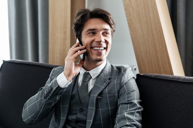 Knappe glimlachende zakenman in pak praten op mobiele telefoon