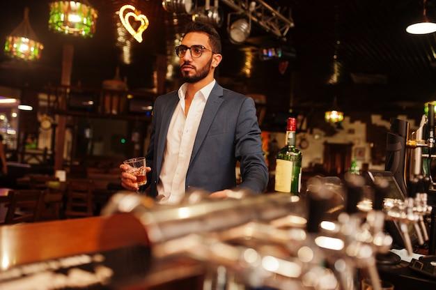 Knappe goed geklede arabische man met glas whisky en sigaar gesteld in pub.