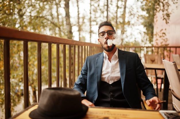 Knappe goed geklede arabische man rook sigaar op balkon van pub.