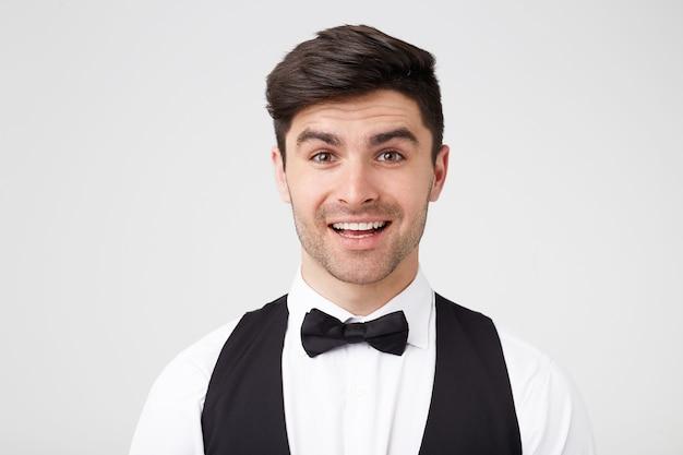 Knappe goed uitziende stijlvolle smarty geklede man lacht aangenaam naar de camera. vriend van de man is naar een feestje gekomen, heeft hem bezocht