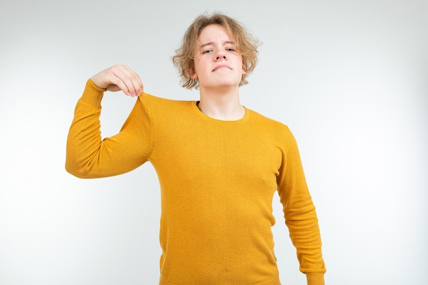 Knappe golvende blonde jongeman in een gele trui houdt vast aan zijn katoenen trui op een witte achtergrond.