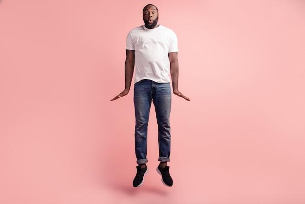 Knappe grappige gekke man springen op roze achtergrond