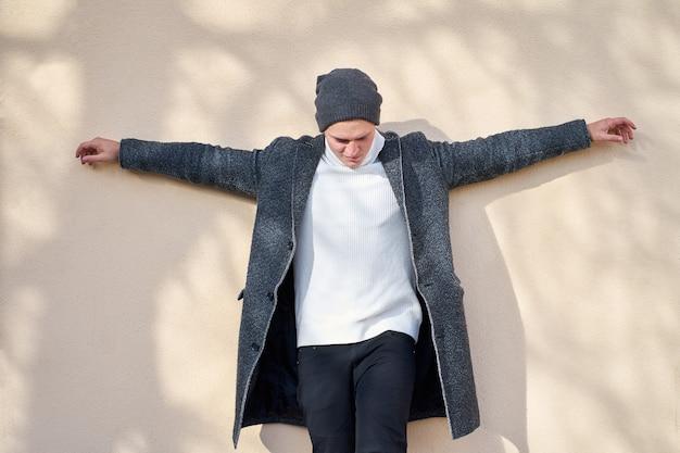 Knappe grappige hipster stijlvolle man met een trendy grijze jas, stijlvolle witte trui veel plezier en poseren op beige muur