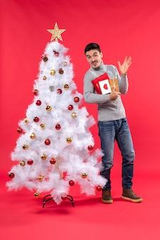 Knappe grappige jongeman permanent in de buurt van de versierde witte nieuwjaarsboom en houdt zijn geschenken