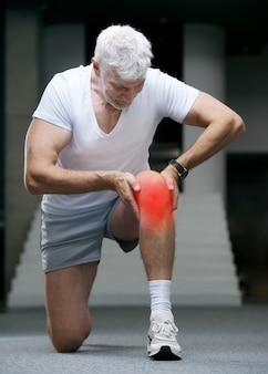 Knappe grijsharige senior man gewond knie of been sport en gezondheidszorg concept