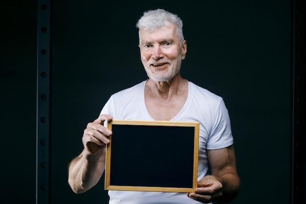 Knappe grijsharige senior man met bord in zijn handen sport- en gezondheidszorgconcept