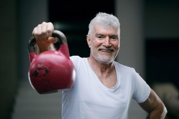 Knappe grijsharige senior man met kettlebell gewicht sport en gezondheidsconcept