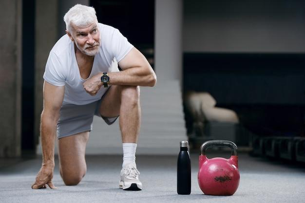 Knappe grijsharige senior man met kettlebell gewicht