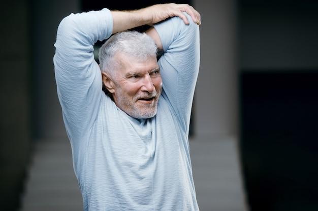 Knappe grijsharige senior strekt zich uit en kneedt de hand sport- en gezondheidszorgconcept