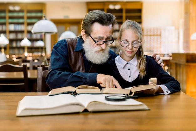 Knappe grootvader lezen van een boek voor zijn schattige kleindochter, haar knuffelen zittend samen aan tafel in vintage oude bibliotheek.