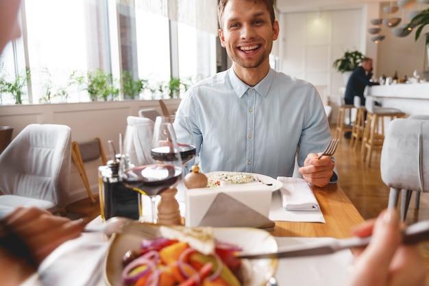 Knappe heer die naar dame kijkt en glimlacht terwijl hij aan tafel zit met heerlijk eten en wijn