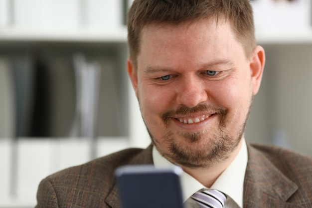 Knappe het glimlachen cellphone van de zakenmanbespreking
