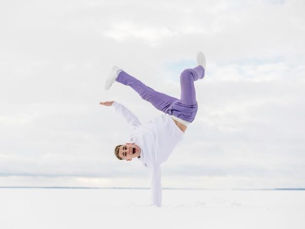 Knappe hiphopdanser buiten in de sneeuw