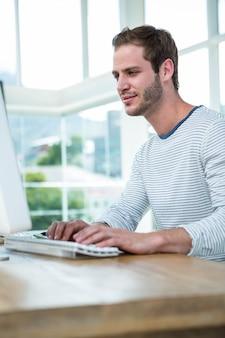 Knappe hipster die aan computer in een helder bureau werkt
