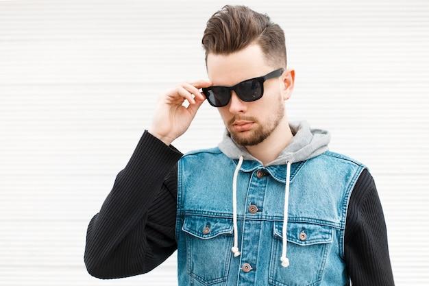 Knappe hipster man in een jeans jasje en zwarte zonnebril in de buurt van een witte houten muur