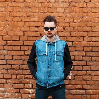 Knappe hipster man in een spijkerjasje in de buurt van een bakstenen muur