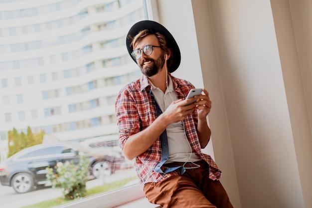 Knappe hipster man met baard in zonnebril sms-berichten via smartphone en bloggen in sociale netwerken delen van multimedia