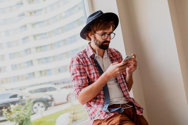 Knappe hipster man met baard in zonnebril sms-berichten via smartphone en bloggen in sociale netwerken