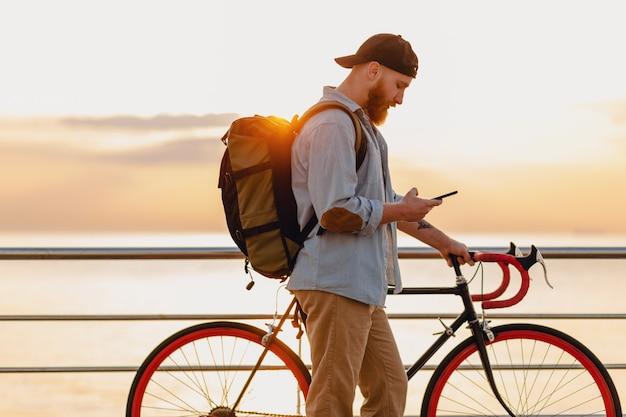 Knappe hipster stijl bebaarde man met behulp van telefoon reizen met rugzak en fiets in de ochtend zonsopgang aan zee, gezonde actieve levensstijl reiziger backpacker