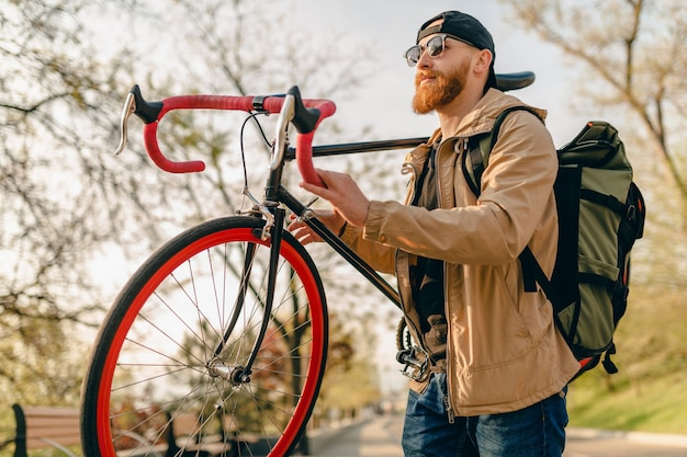 Knappe hipster stijlvolle bebaarde man in jas en zonnebril alleen lopen in straat met rugzak op fiets gezonde actieve levensstijl reiziger backpacker