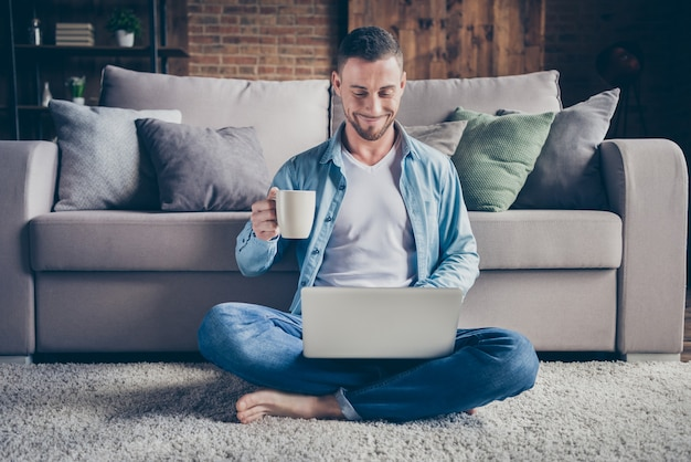 Knappe huiselijke man ontspannen zittend tapijt drinken koffie browsen notebook