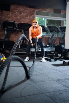 Knappe indiase aziatische jongeman die gevechtstouwoefening doet tijdens het trainen in de sportschool, selectieve focus